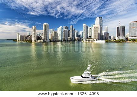 Aerial view of Miami skyscrapers with blue cloudy sky boat sailing next to Miami downtown