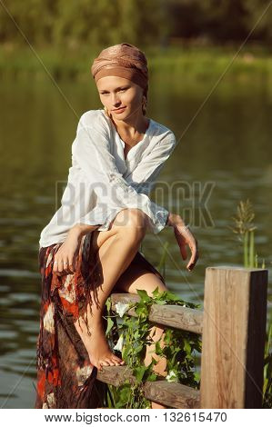 girl in turban and a white blouse sitting at the lake