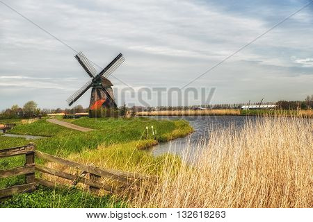 Dutch Windmill along a small canal in polder Schermer Netherlands