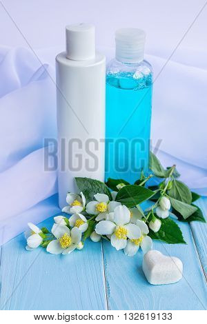Face skin care cosmetic products - lotion and tonic in bottles, flowers, white cloths and beads on a painted blue wooden background