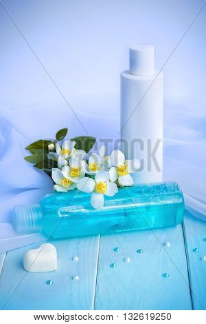 Lotion and tonic in bottles, flowers, white cloths, heart shaped soap and beads - using jasmine essence for cosmetic products concept
