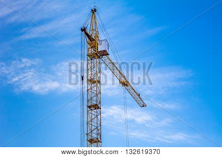 Crane against the blue sky. Yellow crane at the construction site.
