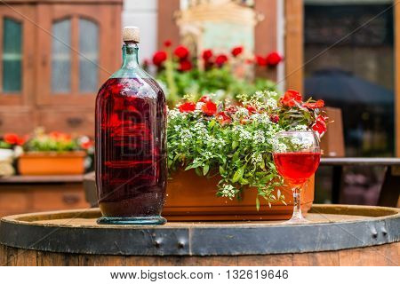 Wine in old vintage bottle on a barrel with flowers.