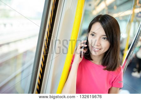 Woman talk to cell phone in train compartment