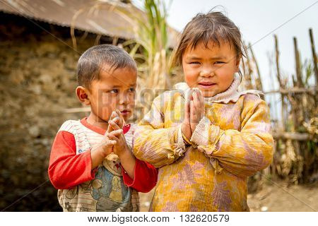 Chisapani Nepal - March 26, 2016 : Happy smiling children of rural village of Nepal are welcoming tourists with shyness on their faces.