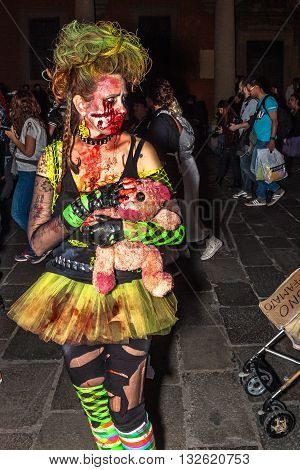 Bologna, Italy - May 21, 2016: Bologna zombie apocalypse walk: zombie woman with bloody doll.
