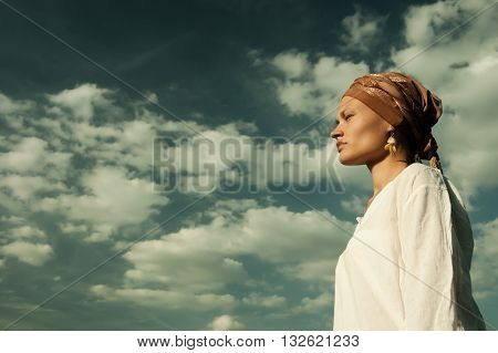 girl in a turban and a white blouse on sky background