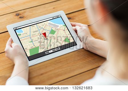 technology, people and navigation concept - close up of woman with gps navigtor map on tablet pc computer screen on wooden table