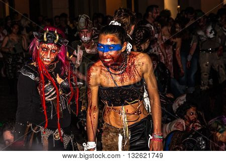 Bologna, Italy - May 21, 2016: Bologna zombie apocalypse walk: a wild and primitive zombie woman during a parade through the center of the city.