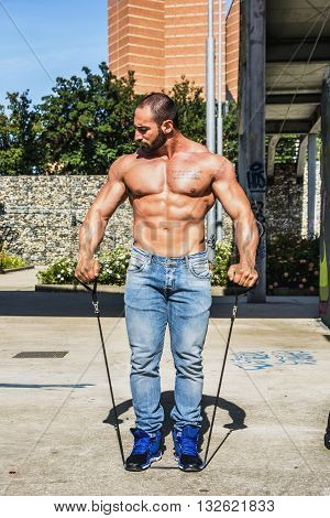 Gorgeous Shirtless Male Bodybuilder Exercising with Elastic Bands, Lifting Weights Outdoor. Showing Healthy Body While Looking away