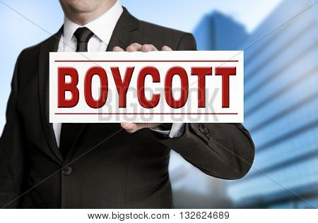 boycott shield is held by businessman background