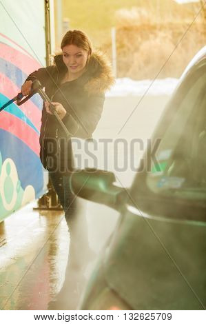 Manual auto wash. Young attractive blonde woman washing the dirty car with foam and pressured water at service station on open air