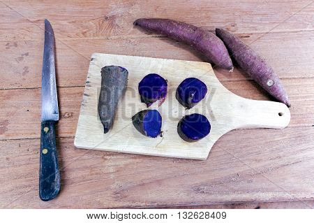 Steamed purple sweet potato split and raw potato on wood
