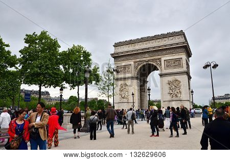 Paris France - May 14 2015: Tourist visit Arc de Triomphe de l'Etoile in Paris. Arc de Triomphe was built in 1806-1836 by architect Jean Shalgrenom by order of Napoleon to commemorate victories of his Army.