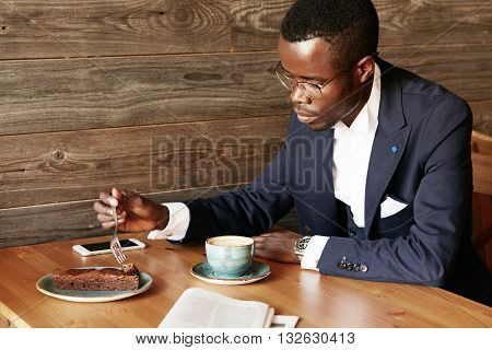 African Corporate Worker In Formal Suit And Spectacles Eating Cake And Drinking Coffee After Hard Wo