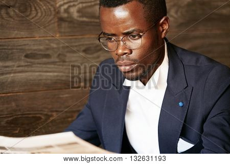 Portrait Of Young African Entrepreneur In Formal Clothes Reading Financial Newspaper With Serious An