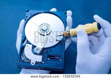 Technician repairing an hard disk on blue background