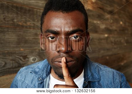 Headshot Of Young African Man In Stylish Clothes Holding Finger On Lips, Asking To Be Quiet Or Keep