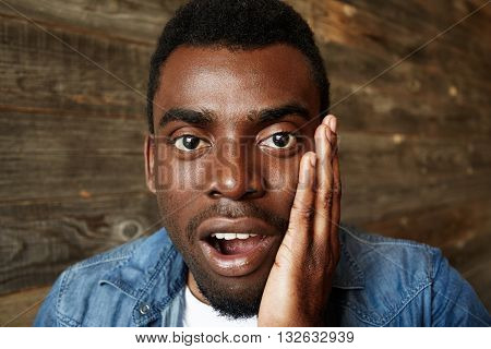 Close Up Shot Of Shocked Handsome African American Student Wearing Denim Shirt Looking In Full Disbe