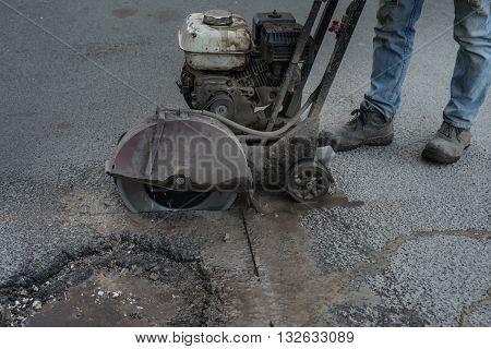 Worker Cuts A Piece Of Asphalt Using A Cutting Machine Pavement.