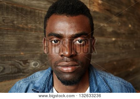 Close Up Isolated View Of Handsome Serious Young African Male Wearing Denim Shirt Looking With Conce