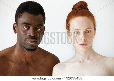 Black And White. Headshot Of African Man And Caucasian Woman Standing Shirtless And Looking At The C