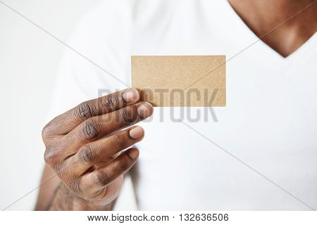 Confident African Entrepreneur In White T-shirt Giving Business Card To You. Close Up View Of Black