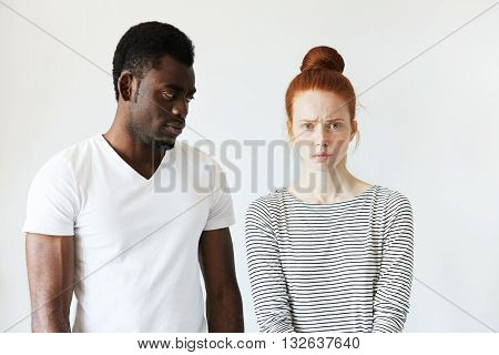 Extraordinary Young Interracial Couple. Beautiful Caucasian Woman Looking At The Camera With Offende