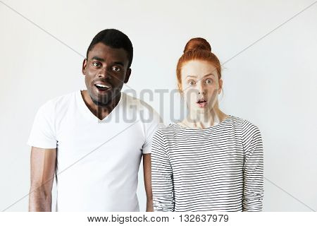 Interracial Friendship. African Man Looking At The Camera With Surprised Expression, Standing Next T
