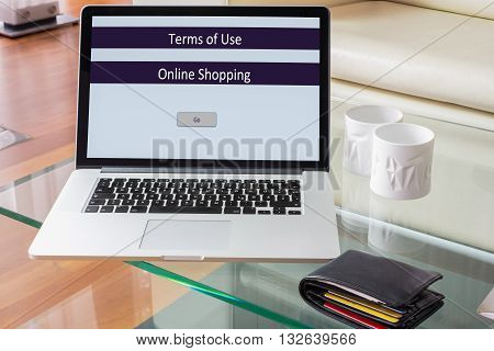 Laptop standing on glass table- terms of use online shopping