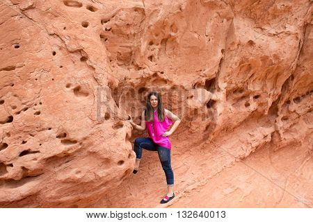 The young woman posing at Valley of Fire State Park USA. The Valley of Fire State Park is the oldest state park in Nevada USA and was designated as a National Natural Landmark in 1968.