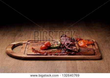 Grilled chicken fillet with roasted vegetables: sliced vegetable marrow, bell pepper and fresh cherry tomatoes with red sauce on wooden board on rustic wooden counter