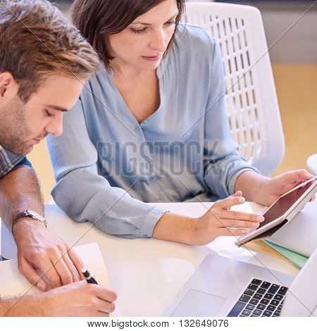 Caucasian man taking notes from his female tutor as she explains work to him using her tablet to present slides to him
