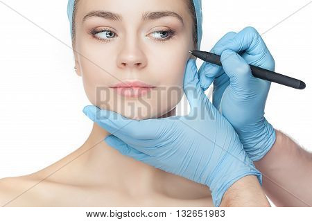 Beautiful young woman before plastic surgery operation. Beautician touching woman face.