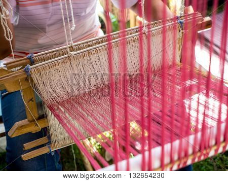 Thai local people make Thai cloth on weaving apparatus