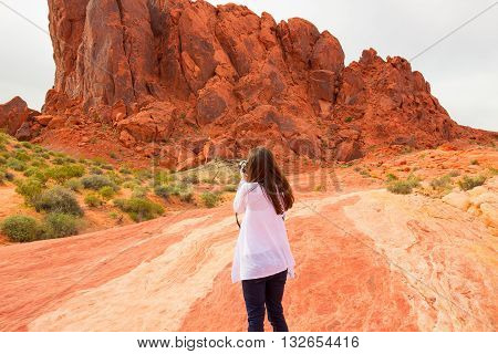 The female tourist taking photos. Girl travel photographer in Valley of Fire State Park Nevada USA