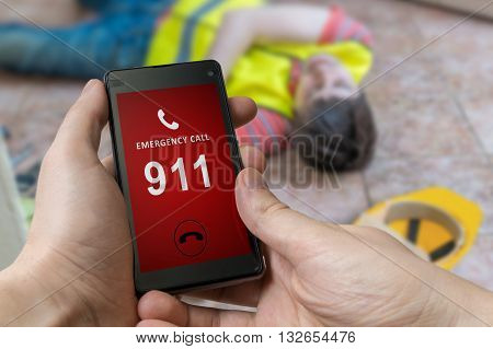 Man Dialing Emergency (911 Number) On Smartphone. Injured Worker