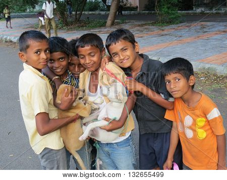 Pune India - October 7 2013: Small Indian kids having fun with their pet dogs.