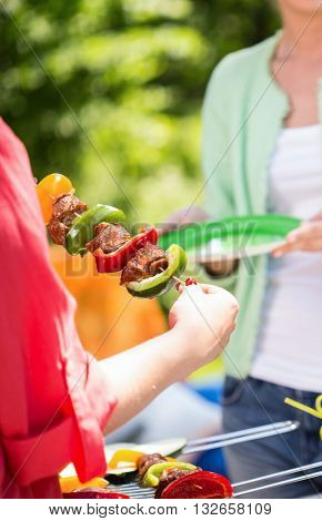 Man grilling shashliks with vegetables in the garden