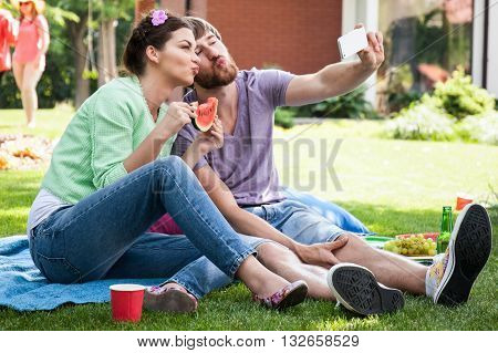 Man and woman puckering up and taking a self-portrait with mobile phone