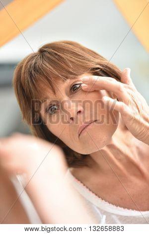 Senior woman applying eye concealer