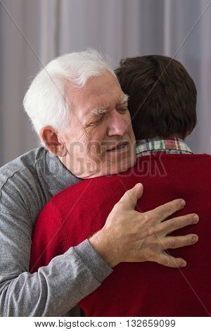 Seniorand illness  man embracing his young son.