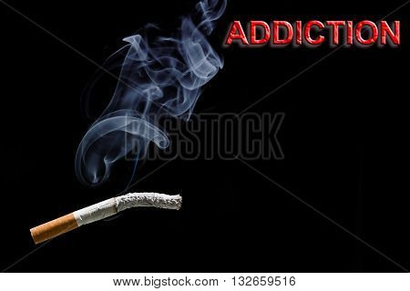 Burned cigarette and red text addiction on black background