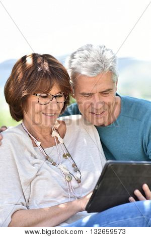 Senior couple using tablet in yard