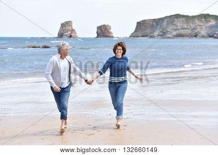 Senior couple running on a sandy beach