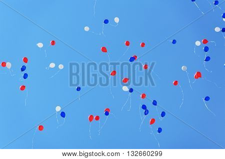 White blue and red baloons flying high in clear blue sky horizontal