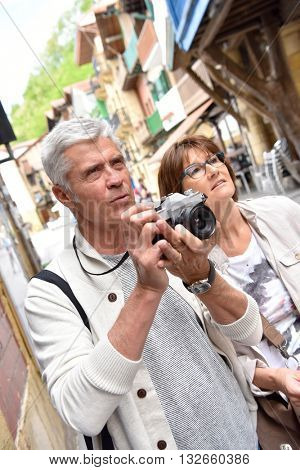 Senior couple of tourists taking pictures during tour