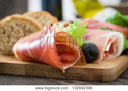 Spanish serrano ham and sausages on a rustic wooden table