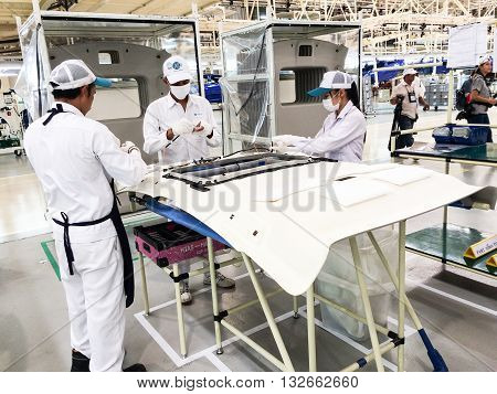 PRACHINBURI Thailand - May 12 2016: Employees of Honda Automobile Thailand work on a assembly line of car body parts at Prachinburi plant in Rojana Industrial Park.