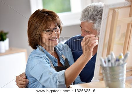 Senior woman painting on canvas, husband beside